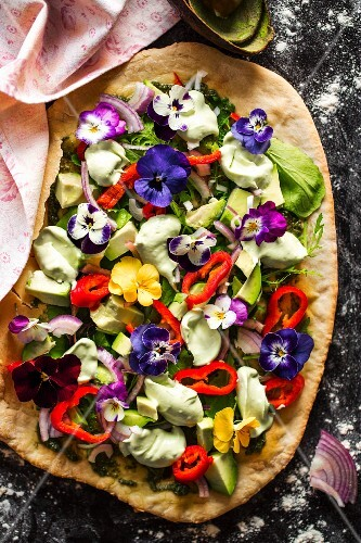 Avocado salad with edible flowers, peppers, red onions and lettuce on a blind-baked pizza base