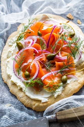 A blind-baked pizza base topped with cream cheese, smoked alpine salmon, dill, red onions and capers