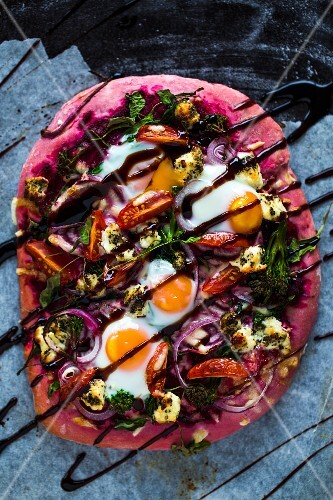 Beetroot pizza dough with broccolini, red onions, tomatoes, goat's cheese, rocket, cheese, fired eggs and balsamic cream
