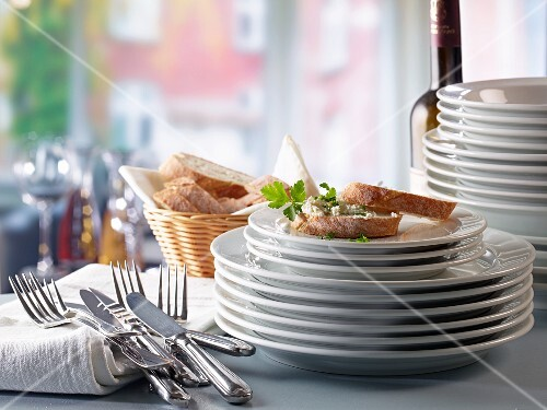 A stack of plates, cutlery and baguette with cream cheese