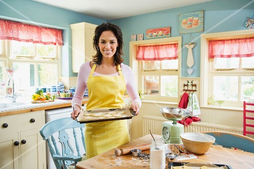 A woman wearing an apron holding a tray of unbaked biscuits