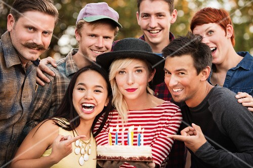 A group photo of friends with a birthday cake