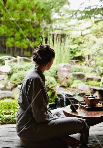 A woman sitting cross-legged at a small tea table in a zen garden
