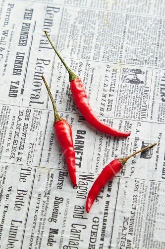 Three fresh chillis on a newspaper