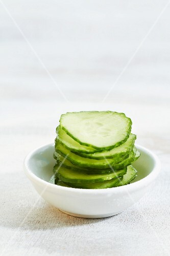 A stack of cucumber slice on a bowl