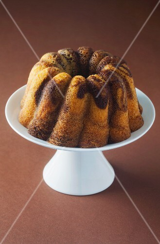 A Bundt cake on a cake stand on a brown surface