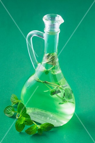Mint syrup in a bottle on a green surface