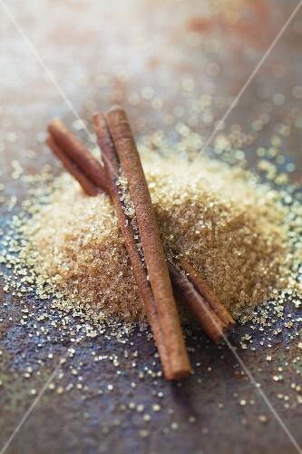 Brown sugar and cinnamon sticks on a metal surface