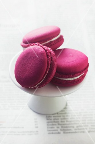 Red macaroons on a white cake stand