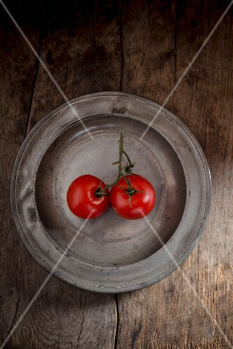 Two tomatoes on a metal plate
