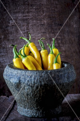 Fresh yellow chillis in a mortar