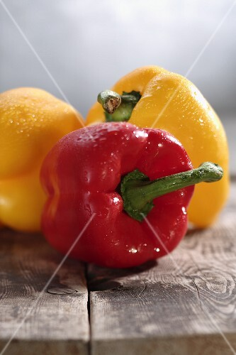 Freshly washed red and yellow peppers on a wooden table