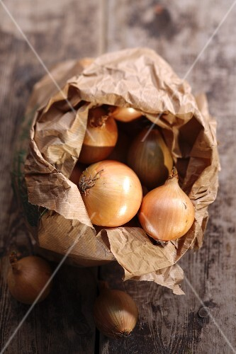 Onions in a paper bag on a wooden surface