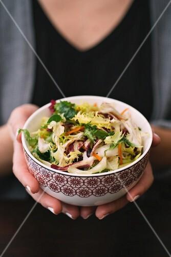Frau hält Salatschüssel mit gemischten Blattsalaten