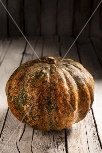 A whole pumpkin on a rustic wooden surface
