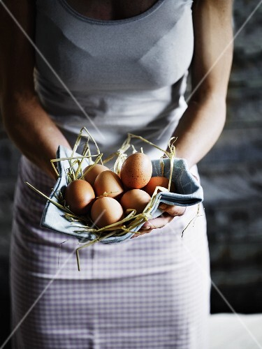 A woman holding a eggs and straw in a cloth in both hands