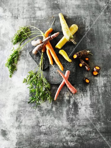 Colourful carrots, some with leaves and some sliced