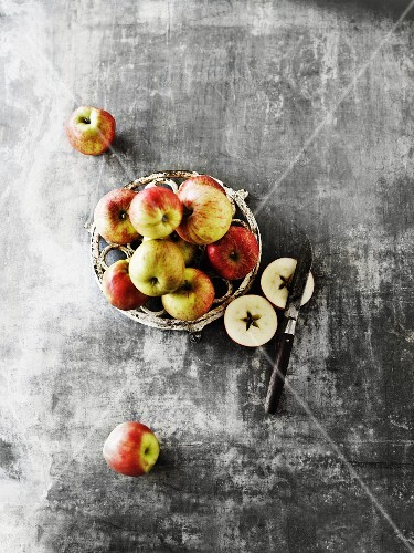 Whole apples on a pot holder, with apples and sliced apples with a knife next to it