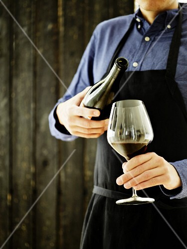 A sommelier with a glass and a bottle of red wine