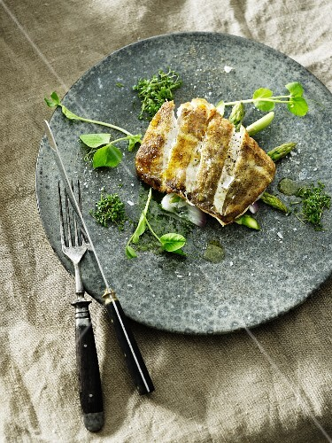 Fried fish fillet on a bed of green asparagus with fresh herbs