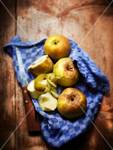 Organic apples on a tea towel with a knife