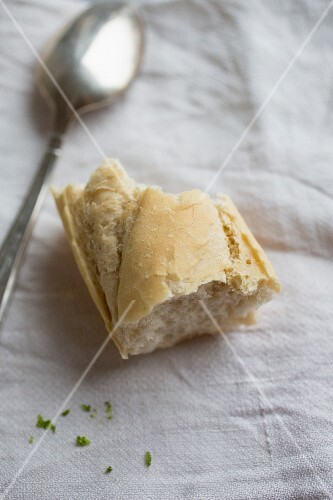 A piece of baguette with a spoon on a linen cloth