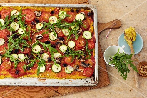 Polenta pizza with courgette, tomatoes, olives and rocket