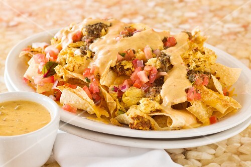 Breakfast nachos with egg, chorizo, tomatoes and melted cheese