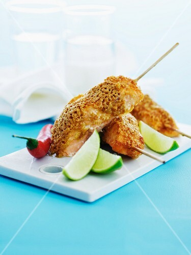 Three fried salmon skewers with limes and chilli on a chopping board