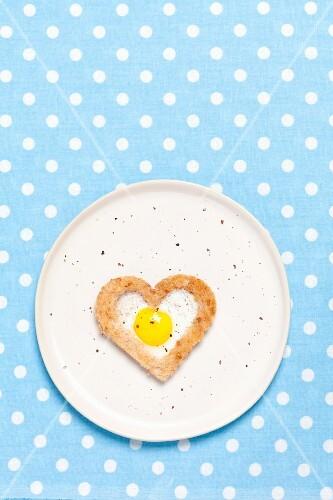 A fried quail's egg baked into a heart-shaped slice of toast