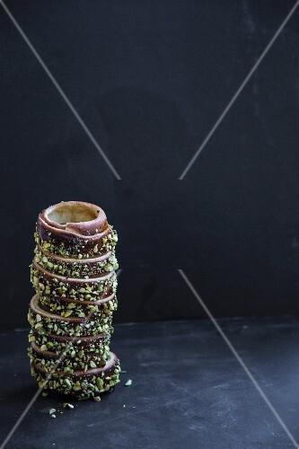 Kürtőskalács (or kurtos kalacs, chimney cake) with chocolate and chopped pistachio nuts