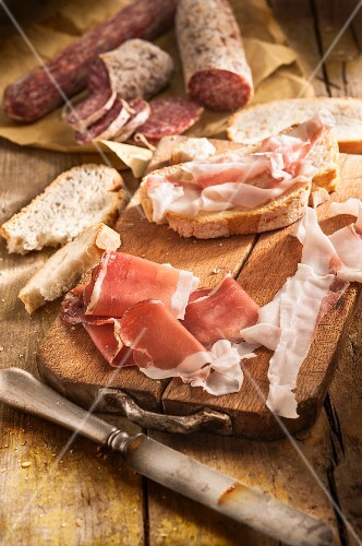 Bacon, salami and bread on a chopping board
