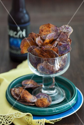 Purple potato crispy in a glass with a bottle of beer in the background