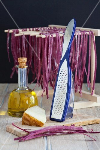 Beetroot pasta hung to dry with olive oil and cheese