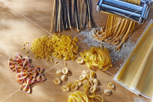 Various types of pasta and a pasta machine on a wooden table