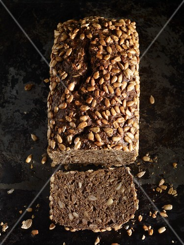 A loaf of sunflower seed bread, sliced, seen from above