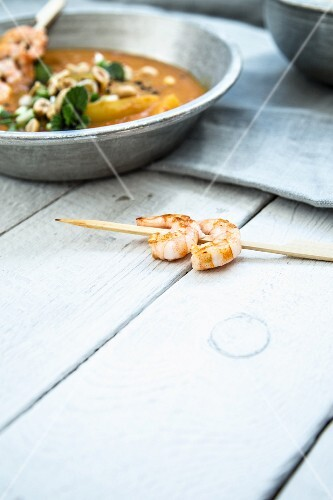 Cucumber curry with peanuts and prawn skewers