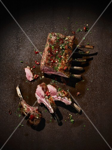 Grilled saddle of lamb on a brown metal surface with herbs and chilli