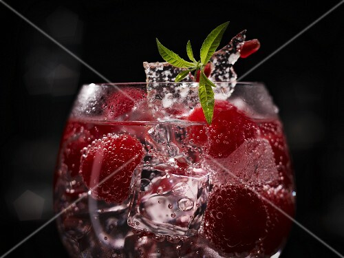 An exotic raspberry drink with whole raspberries, ice cubes and sugar decoration with pomegranate seeds
