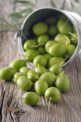 Green olives on a rustic wooden surface