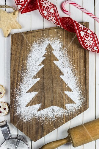A Christmas tree print in icing sugar on a chopping board