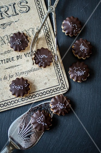 Nut biscuits with chocolate glaze and silver pearls