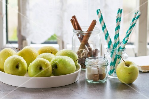 Green apples, sugar cubes and cinnamon sticks on a kitchen table