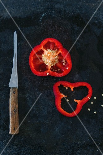 A sliced red pepper and a knife on a metal surface