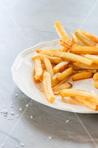 Chips on a white plate with sea salt