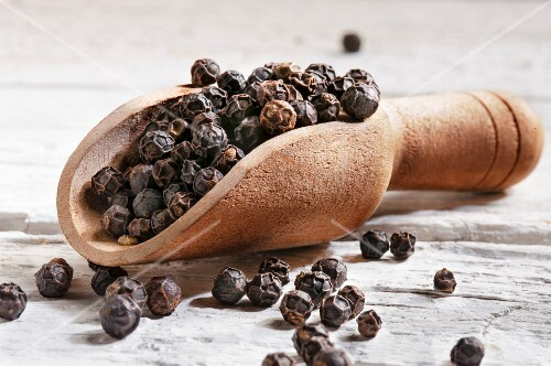 Black peppercorns in a wooden scoop
