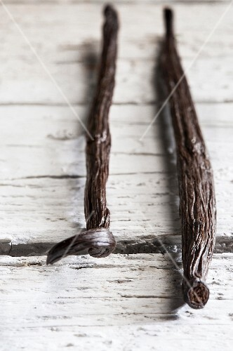 Three vanilla pods on a wooden surface