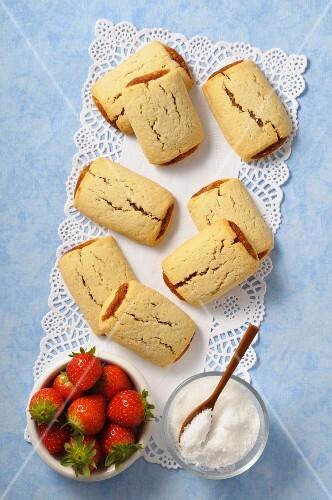 Strawberry cakes, sugar and fresh strawberries