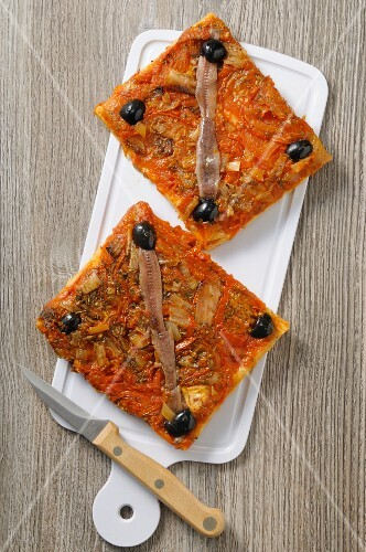 Two slices of pizza with anchovies and olives