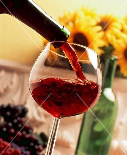 Red wine being poured into a glass with sunflowers in the background